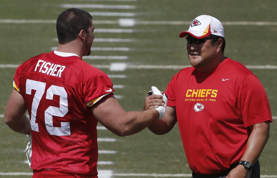 Kansas City Chiefs tackle Eric Fisher (72) shakes hands with assistant offensive line coach Eugene Chung, right, during NFL football training camp in St. Joseph, Mo., Friday, July 26, 2013. (AP Photo/Orlin Wagner)
