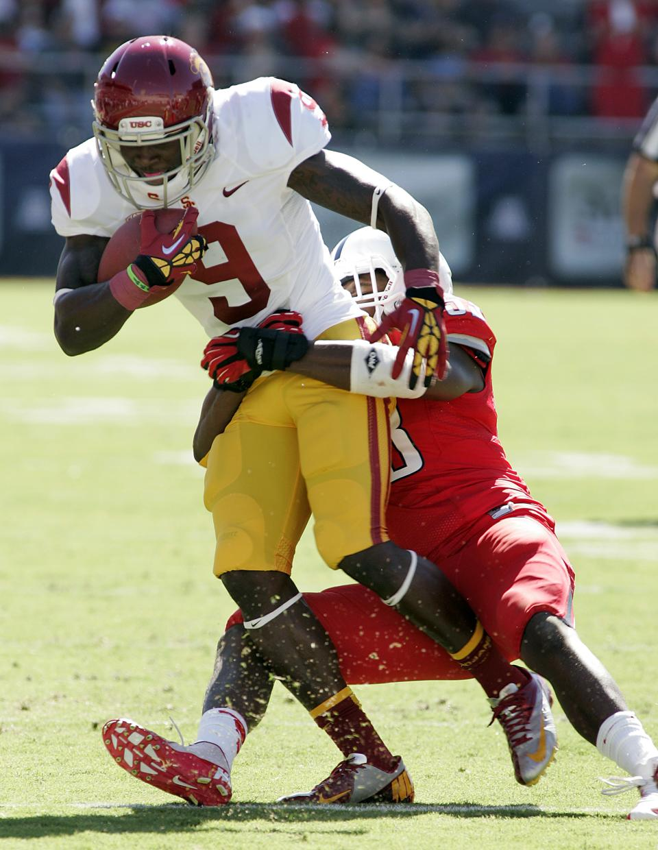 Southern California's Marqise Lee (9) is dragged down near the sidelines by Arizona's Sir Thomas Jackson, right, during the first half of an NCAA college football game at Arizona Stadium in Tucson, Ariz., Saturday, Oct. 27, 2012. (AP Photo/John Miller)