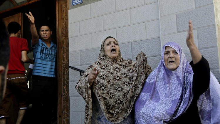Palestinians over come by emotion arrive at a mosque for shelter after an Israeli strike hit Gaza City, northern Gaza Strip, Thursday, Aug. 21, 2014. (AP Photo/Adel Hana)