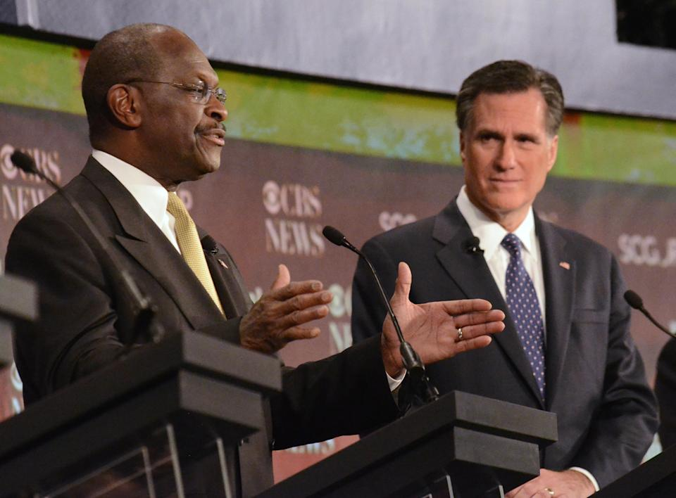 Republican presidential candidates Herman Cain, left, speaks as Mitt Romney,  looks on during the  CBS News/National Journal foreign policy debate at the Benjamin Johnson Arena, Saturday, Nov. 12, 2011 in Spartanburg, S.C. (AP Photo/Richard Shiro)