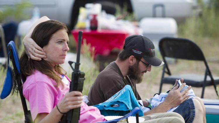 "Shelton interacts with his son as his mother holds his rifle during a Bundy family ""Patriot Party"" near Bunkerville, Nevada"