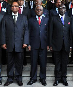 In this handout photo supplied by the South African Government Communications and Information Services, (GCIS) presidents Jacob Zuma, of South Africa, left, Armando Guebuza, center, of Mozambique and Robert Mugabe of Zimbabwe, right, at a special summit on Zimbabwe in Mozambique Saturday, June 15, 2013. Regional presidents opened the special summit after President Robert Mugabe set crucial elections for the end of July, despite opposition from the country's prime minister. (AP Photo/Kopano Tlape - GCIS)
