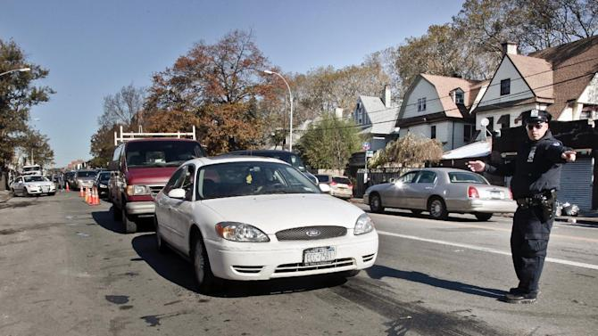 Police direct cars in line to gas station pumps on Friday, Nov. 9, 2012 in Brooklyn, N.Y.  Police were at gas stations to enforce a new gasoline rationing plan that lets motorists fill up every other day that started in New York on Friday morning. (AP Photo/Bebeto Matthews)