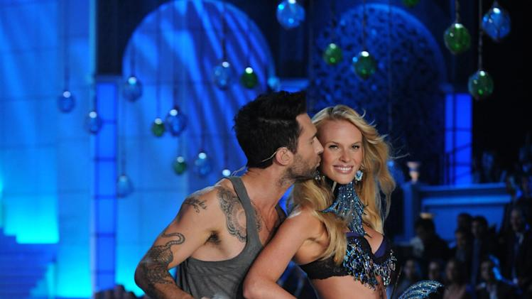 Adam Levine kisses a model as he performs during the Victoria's Secret fashion show in New York, Wednesday, Nov. 9, 2011. (AP Photo/Brad Barket)