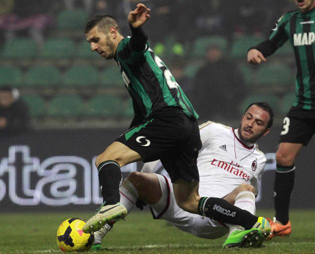 AC Milan's Pazzini fights for the ball with Sassuolo's Marzorati during their Italian Serie A soccer match in Reggio Emilia