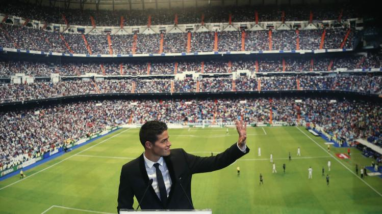 Colombia's soccer player James Rodriguez waves to fans during his presentation at the Santiago Bernabeu stadium in Madrid