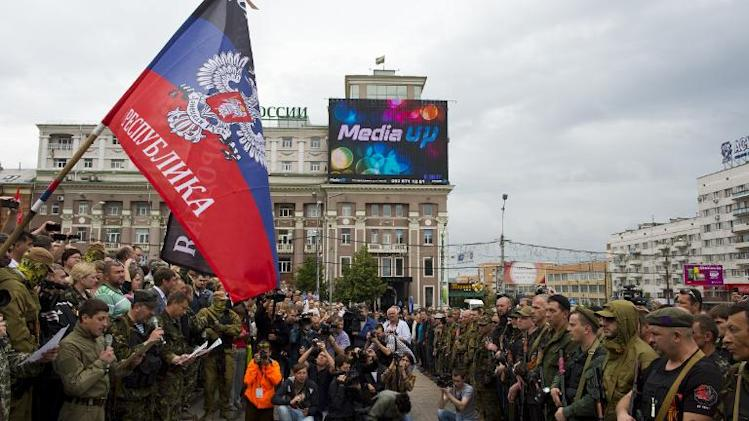 """New army recruits stand in front of a flag of the self-proclaimed """"Donetsk People's Republic"""" during an oath taking ceremony on Lenin Square in Donetsk, June 21, 2014"""