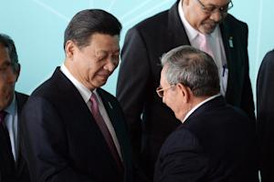 China's President Xi Jinping (L) chats with Cuba's…