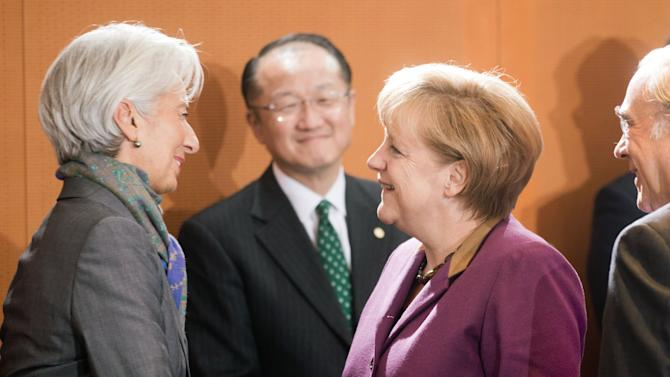 German chancellor, Angela Merkel, second right, welcomes International  Monetary Fund  (IMF) chief Christine Lagarde, left, while World Bank head Jim Yong Kim, center,  looks on, in Berlin, Tuesday Oct. 30, 2012.  (AP Photo / Kay Nietfeld , Pool)