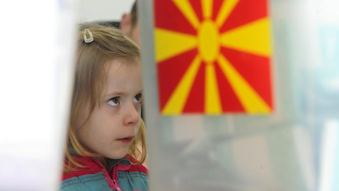 A girl looks at a ballot box for local elections, at a polling station in Skopje, Macedonia, on Sunday, March 24, 2013. The small Balkan country hopes that free, transparent and peaceful local elections will help it strengthen its case for European Union membership. (AP Photo/Boris Grdanoski)