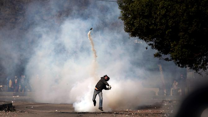 A protester throws a tear gas canister back at riot police during clashes near Tahrir Square, in Cairo, Sunday, Jan. 27, 2013. Clashes continued for the fourth successive day between protesters and police near Tahrir square, birthplace of the 2011 uprising. Police used tear gas, while the protesters pelted them with rocks. (AP Photo/Khalil Hamra)