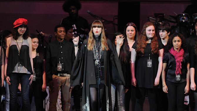 """Singer Diane Birch, center, and a choir perform at """"The Music of Prince"""" tribute concert at Carnegie Hall on Thursday March 7, 2013 in New York. (Photo by Evan Agostini/Invision/AP)"""