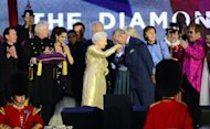Prince Charles kisses the hand of Britain's Queen Elizabeth II on stage as British singers Paul McCartney (3rd R) and Elton John (R) and other performers look on after the Jubilee concert at Buckingham Palace