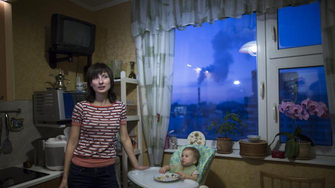 Olga Kupriyanova, a 35-year-old law professor at Moscow State University speaks to the Associated Press, next to her one year old doughtier Tartyana, at home in Moscow, Russia, Tuesday, Dec. 2, 2014. Russia's economy has been battered this year by uncertainty over the conflict in Ukraine, the falling price of oil, Western sanctions and retaliatory Russian import bans which have poor and middle-class Russians feeling the pinch. (AP Photo/Alexander Zemlianichenko)