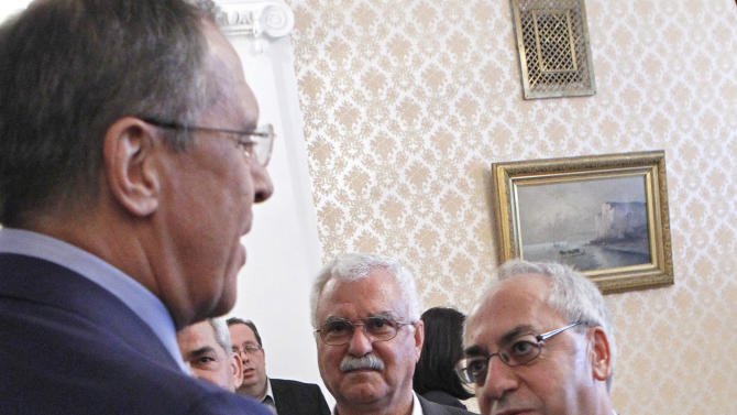 Russian Foreign Minister Sergey Lavrov, left, shakes hands with a leader of the Syrian National Council (SNC), Abdulbaset Sieda in Moscow, Russia, Wednesday, July 11, 2012. (AP Photo/Misha Japaridze)