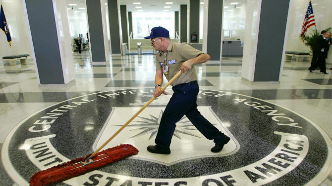 a workman slides a dust mop over the floor at the Central Intelligence Agency headquarters