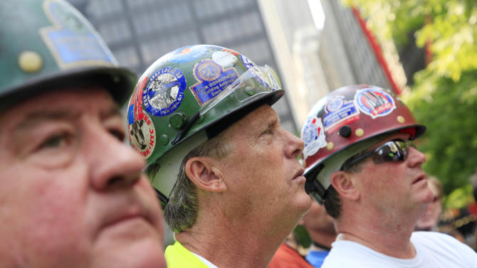 Ironworkers Martin Duffy, left, Barry Collins, center, and Dennis Byrnes attend  a ceremony for the September 11 cross, Saturday, July 23, 2011 in New York.  After the ceremony, the cross was installed at the National September 11 Memorial and Museum. It was discovered upright in the ruins of ground zero following the attacks of September 11, 2001. (AP Photo/Mark Lennihan)