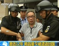 This TV screen grab from CCTV shows Lai Changxing escorted by Chinese authorities after he landed in Beijing aboard a civilian flight in July 2011. A Chinese court Friday handed a sentence of life in jail to Lai, the boss of a smuggling and bribery scam, Xinhua said