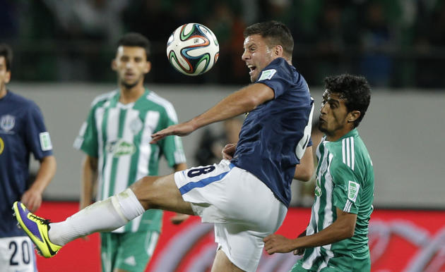 Auckland City FC's Christopher Bale, center, battles for the ball with Raja Casablanca's Chemseddine Chtibi during the opening game of the FIFA Club World Cup soccer tournament in Agadir, Moro