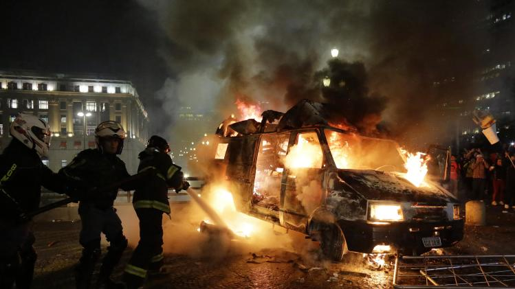 Firefighters work to put out a burning vehicle set on fire by protestors, in front of City Hall in Sao Paulo, Brazil, Tuesday, June 18, 2013. On Tuesday, thousands of people marched on Sao Paulo's City Hall building, where a small group fought police in an unsuccessful attempt to force their way in. Some of the biggest demonstrations since the end of Brazil's 1964-85 dictatorship have broke out across this continent-sized country, uniting multitudes frustrated by poor transportation, health services, education and security despite a heavy tax burden. (AP Photo/Nelson Antoine)