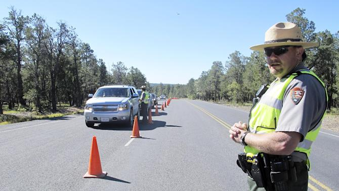 Grand Canyon National Park Ranger Jason Morris surveys traffic backed up at the closed park entrance on Thursday, Oct. 3, 2013 in Ariz. More than 400 national parks are closed as Congress remains deadlocked over federal government funding. (AP Photo/Brian Skoloff)
