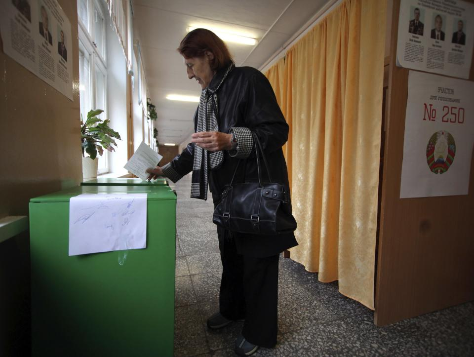 Belarusian woman casts her ballot paper at a polling station during parliamentary elections in Minsk, Belarus, Sunday, Sept. 23, 2012. Belarus is holding parliamentary elections Sunday without the main opposition parties, which boycotted the vote to protest the detention of political prisoners and opportunities for election fraud. (AP Photo/ Dmitry Brushko)