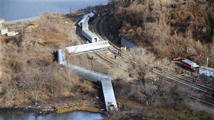 Emergency workers examine the site of a Metro North train derailment in the Bronx borough of New York