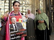 An Egyptian woman named Tahani holds a poster of ousted president Hosni Mubarak as she stands outside the military hospital where he was transfered after suffering a stroke in prison