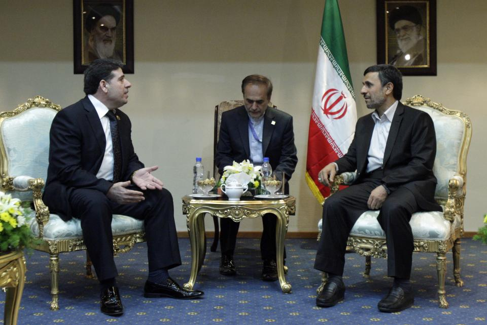 Syria's prime minister, Wael Nader al-Halqi, left, talks with Iranian President Mahmoud Ahmadinejad, right, during their meeting on the sideline of the Nonaligned Movement summit in Tehran, Iran, Friday, Aug. 31, 2012. An unidentified interpreter sits at center. (AP Photo/Vahid Salemi)