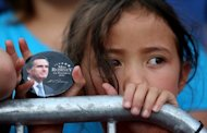 A young supporter of Republican presidential candidate Mitt Romney holds a campaign button during a campaign rally in Norfolk, Virginia