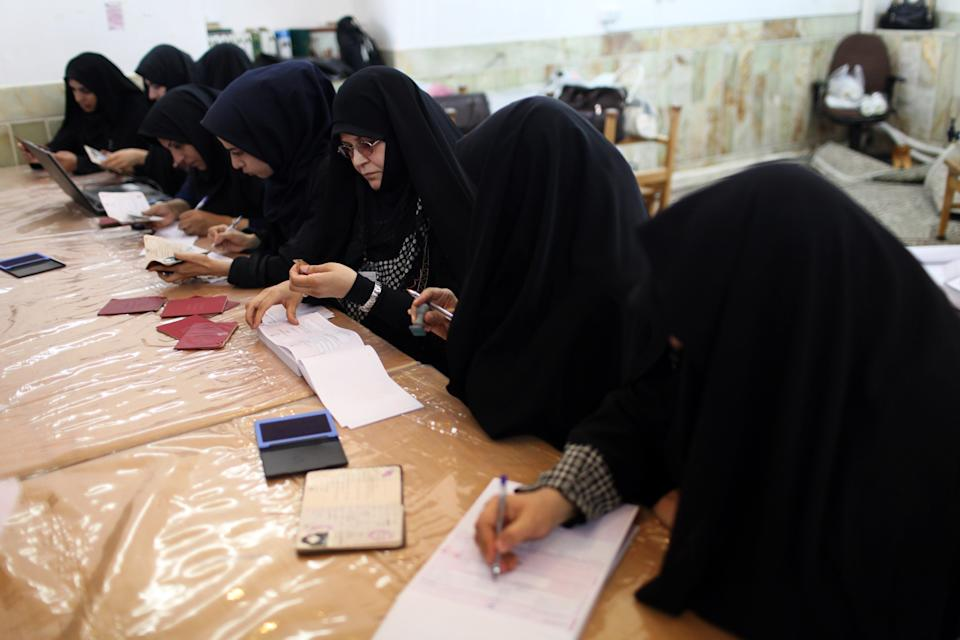 Women attend a polling station to vote during presidential elections in Qom, 125 kilometers (78 miles) south of the capital Tehran, Iran, Friday, June 14, 2013. (AP Photo/Ebrahim Noroozi)