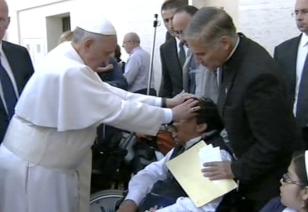 In this image made from video provided by APTN, Pope Francis lays his hands on the head of a young man on Sunday, May 19, 2013, after celebrating Mass in St. Peter's Square. The young man heaved deepl