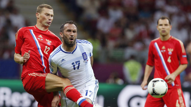 Russia's Alexei Berezutski, left, is challenged by Greece's Fanis Gekas during the Euro 2012 soccer championship Group A  match between Greece and Russia in Warsaw, Poland, Saturday, June 16, 2012. (AP Photo/Thanassis Stavrakis)