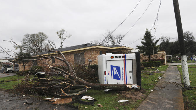 A U.S. Postal truck lies on its side in the yard of a home in Rayne, La., after a suspected tornado hit the area injuring at least nine people, leveling homes and causing natural gas leaks that prompted evacuations on Saturday, March 5, 2011. (AP Photo/The Lafayette Daily Advertiser, P.C. Piazza) MANDATORY CREDIT