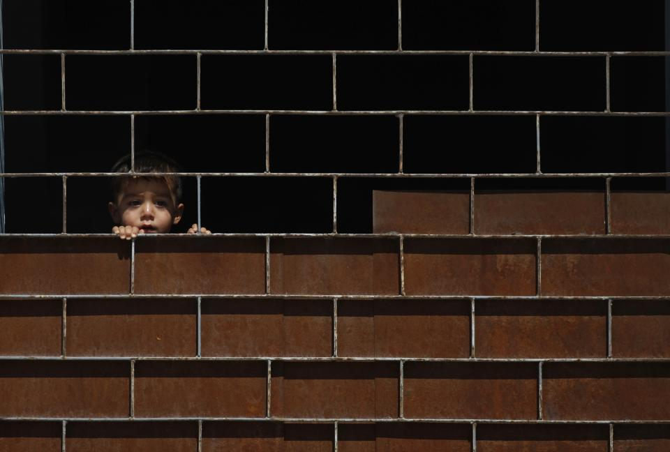 A Syrian boy watches his friends play at a school where they live after they have fled their homes due to the fighting, in the town of Kafr Hamra  ten kilometers .(six miles) north of the center of  Aleppo city, Syria, Tuesday, Aug. 7, 2012. (AP Photo/ Khalil Hamra)