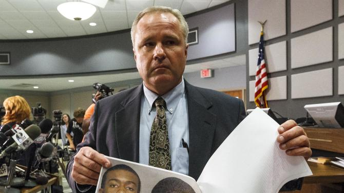 Auburn Police Chief Tommy Dawson shows headshots of suspect Desmonte Leonard, 22, of Montgomery, during a news conference, Sunday, June 10, 2012, in Auburn, Ala. Police say Leonard has been charged with capital murder and has not yet been captured, in connection with a shooting at an apartment complex near Auburn University. Dawson urged Leonard to turn himself in and also said authorities were searching for two other persons of interest. (AP Photo/Opelika-Auburn News, Vasha Hunt)