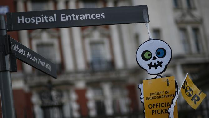 A cartoon skeleton hangs from a hospital sign on a picket line outside Manchester Royal Infirmary in Manchester, northern England