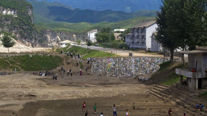 In this Monday, Aug 13, 2012 photo, North Koreans practice volleyball in a mud covered field as others work to build a sandbag wall trying to repair damage brought by July flooding in Songchon County, North Korea. Twin typhoons are renewing fears of a humanitarian crisis in North Korea, where poor drainage, widespread deforestation and fragile infrastructure can turn even a routine rainstorm into a catastrophic flood. (AP Photo/David Guttenfelder)