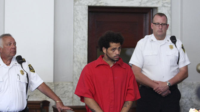 Carlos Ortiz, left, stands in Attleboro District Court for his arraignment on weapons charges, Friday, June 28, 2013 in Attleboro, Mass. Ortiz was arrested Wednesday in Bristol, Conn., in connection with the murder case against former New England Patriots tight end Aaron Hernandez , now charged in the murder of Odin Lloyd. (AP Photo/The Boston Globe, George Rizer, Pool)