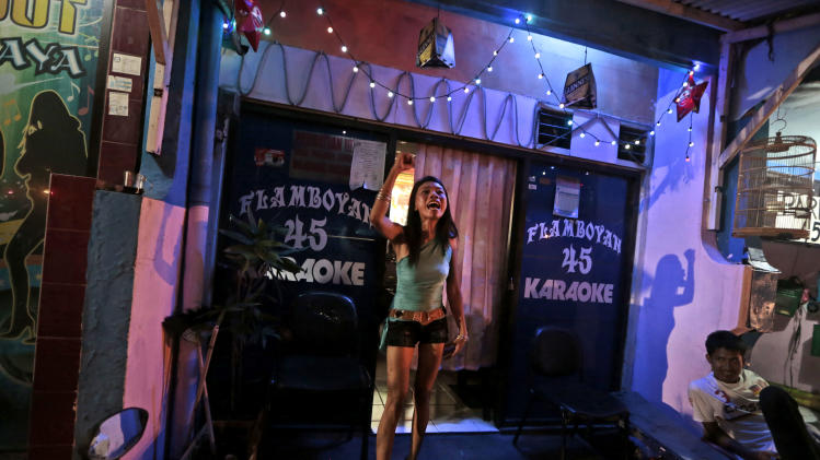 In this Thursday, June 19, 2014 photo, a 'karaoke girl' shouts protests against the city government's move to close down Dolly prostitution complex upon seeing reporters walking past her karaoke parlor at the red-light district in Surabaya, Indonesia. The mayor of Indonesia's second-largest city may have officially shut down one of Southeast Asia's biggest red-light districts areas last week, but the world's oldest profession is still up and running despite warnings to stop. (AP Photo/Dita Alangkara)