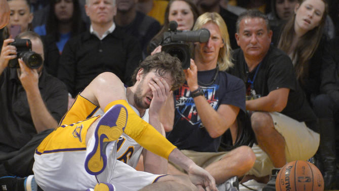 Los Angeles Lakers forward Pau Gasol, of Spain, goes down after being hit in the face by Denver Nuggets center JaVale McGee during the second half of their NBA basketball game, Sunday, Jan. 6, 2013, in Los Angeles. The Nuggets won 112-105. (AP Photo/Mark J. Terrill)
