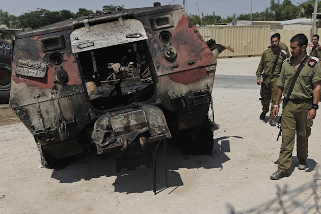 Israeli soldiers look at the wreckage of an Egyptian military vehicle after militants burst it through a security fence into Israel from Egypt, after it was brought to an Israeli military base along the border with Egypt, southern Israel, Monday, Aug. 6, 2012. Officials say Egypt has deployed at least two helicopter gunships to the Sinai Peninsula in the hunt for militants behind the killing of 16 Egyptian soldiers at a checkpoint along the border with Israel. Suspected Islamists on Sunday evening attacked the Egyptian checkpoint, killed the troops, then stole two of their vehicles and burst through a security fence into Israel. Israeli aircraft then halted their assault. (AP Photo/Tsafrir Abayov)