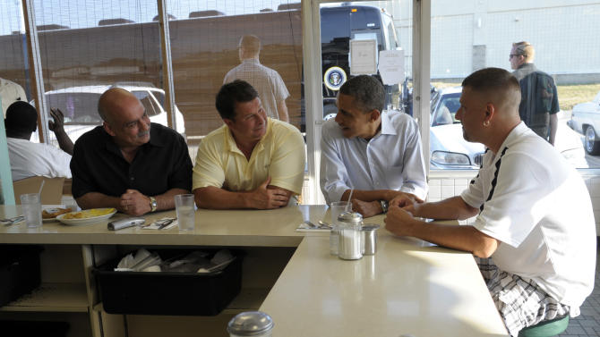 With his campaign bus in the background, President Barack Obama talks with patrons of Ann's Place in Akron, Ohio, Friday, July 6, 2012. From left are, Jim DiFalco, a Goodyear worker from Tallmadge, Ohio; Rick Nixon, a Goodyear worker from Norton, Ohio; the president; and Keith Ross, a Goodyear worker from Norton, Ohio. Obama is on a two-day bus trip through Ohio and Pennsylvania. (AP Photo/Susan Walsh) Rick works in the mix center at the Goodyear plant in Akron. Has worked for Goodyear for almost 20 years and is the Political Coordinator for the UAW Local 2L in Akron.   Jim was first hired at Goodyear in 1980. He was laid off in 1986, then re-hired in 1992 and has worked there ever since. His father and grandmother both worked for Goodyear.   Keith has worked at Goodyear for 14 years where he makes NASCAR racing tires. (AP Photo/Susan Walsh)