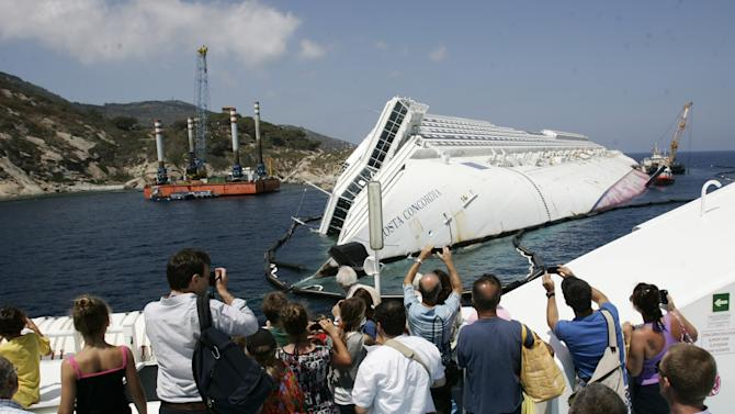 """Tourists take photographs of the Costa Concordia wreckage as they arrive on a ferry to the Giglio Island, Italy, Thursday, July 12, 2012. Works have begun to remove the tons of rocky reef embedded into the Concordia cruise ship's hull, a first step in plans to eventually tow the wreck away from the island, where it ran aground last January. The whole removal process could take as long as a year. In a broadcast interview Tuesday, Concordia's captain Francesco Schettino described the collision as a """"banal accident"""" in which """"destiny"""" played a role. (AP Photo/Gregorio Borgia)"""