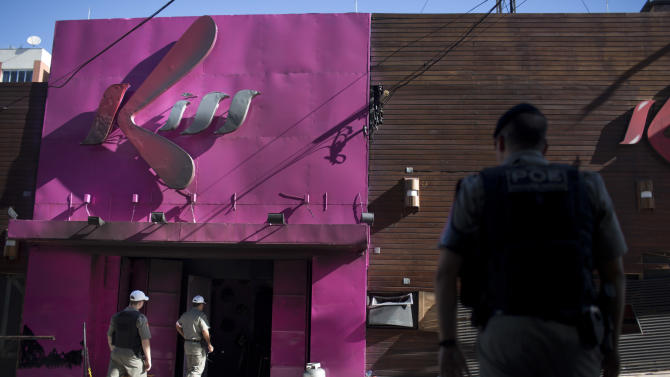 FILE - In this Jan. 28, 2013, file photo, police officers enter the Kiss nightclub after a fatal fire in Santa Maria city, Rio Grande do Sul state, Brazil. Just over a week since the nightclub fire killed nearly 240 revelers in southern Brazil, Carnival festivities hit full stride Friday, Feb. 8, raising questions about the safety of those who will pack party spaces across the nation. (AP Photo/Felipe Dana, file)