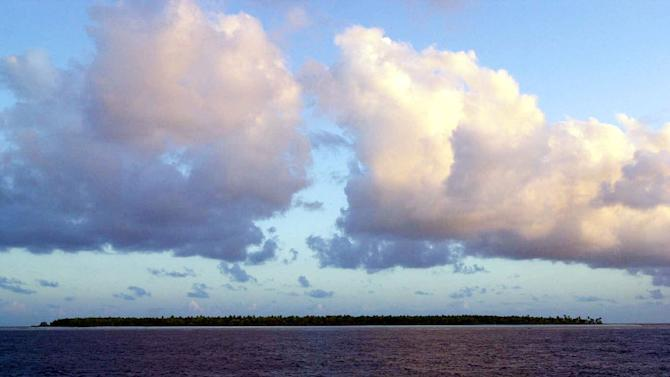 FILE - In this Dec. 30, 1999 file photo, clouds float over the Millennium Island, Kiribati, in the South Pacific. Fearing that climate change could wipe out their entire Pacific archipelago, the leaders of Kiribati are considering an unusual backup plan: moving the populace to Fiji. Kiribati President Anote Tong told The Associated Press on Friday, March 9, 2012 that his Cabinet this week endorsed a plan to buy nearly 6,000 acres on Fiji's main island, Viti Levu. He said the fertile land, being sold by a church group for about $9.6 million, could be insurance for Kiribati's entire population of 103,000, though he hopes it will never be necessary for everyone to leave. (AP Photo/Katsumi Kasahara, File)