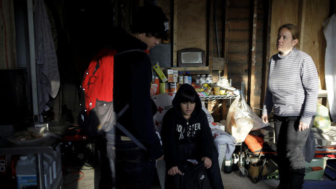 """In this Monday, Dec. 3, 2012 photo, Rachael Alhadad talks with her sons, Ayman Alhadad, 15, left, and Ameer Alhadad, 14, center, as they return home from school at their house in the Midland Beach section of Staten Island, New York. The stress of the past few weeks has taken its toll on the two, who lost all of their school books and supplies in the flooding from Superstorm Sandy on Oct. 29, 2012. """"They just got their report cards, and they're not doing very good at all,"""" Rachael said. """"It's hard to study. Because then you gotta think about, 'Oh no, I gotta go home to the same thing again.'"""" (AP Photo/Seth Wenig)"""