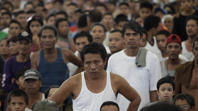 A Filipino man reacts after watching Filipino boxing hero Manny Pacquiao being knocked out by Mexican Juan Manual Marquez during a live satellite broadcast at a multi-purpose hall in suburban Paranaque, south of Manila, Philippines on Sunday Dec. 9, 2012. Many Filipinos have been stunned by Pacquiao's knockout defeat to Marquez, dampening the spirit of a nation battered recently by a powerful typhoon that left more than 600 dead. (AP Photo/Aaron Favila)