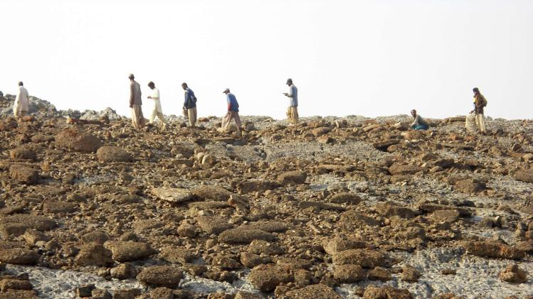 People walk on an island that rose from the sea following an earthquake, off Pakistan's Gwadar coastline in the Arabian Sea