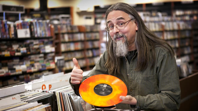 """Chris Bown poses Thursday, April 19, 2012, in Scarborough, Maine, with a copy of The Knack's """"Live in Los Angeles 1978."""" The vinyl record is being released for Record Store Day on Saturday, April 21. Brown, the head of marketing for Bull Moose Music, conceived of the day five years ago. This year there'll be more than 300 new and special releases. (AP Photo/Robert F. Bukaty)"""